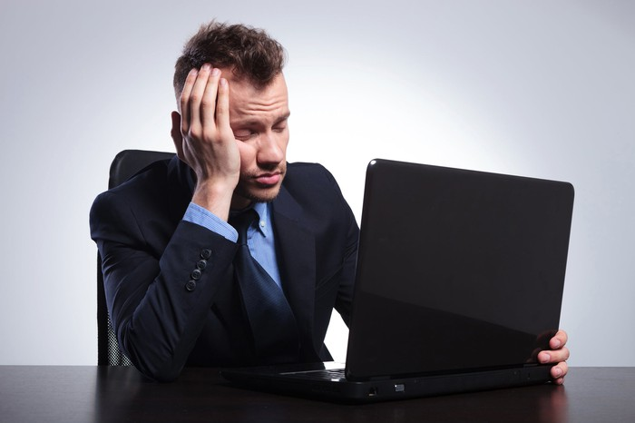 Seated man in suit falling asleep at laptop