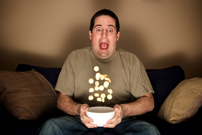 A man on a sofa sits with an open-mouthed expression of surprise, as the food in his bowl flies into the air.