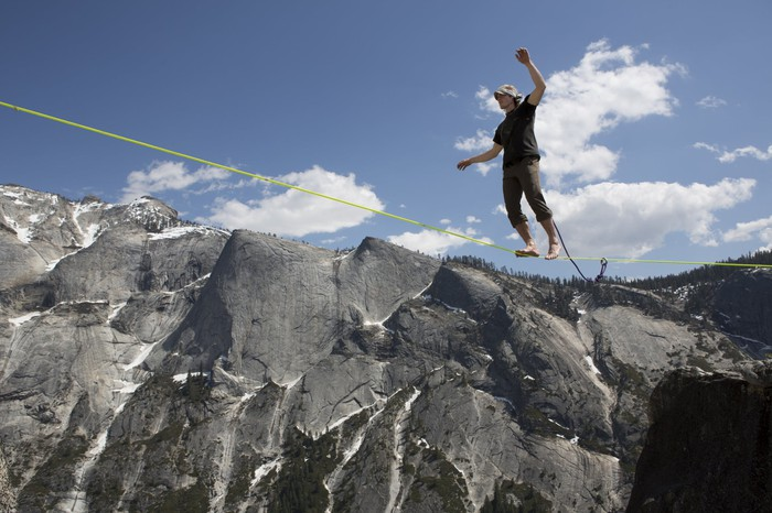 Person walking on a tightrope strung across .a gap in mountains