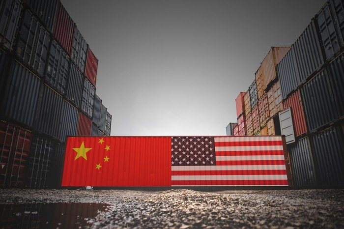 Two containers with a US flag and a China flag on them