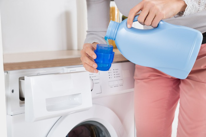 A person measures out laundry detergent in front of a washing machine.