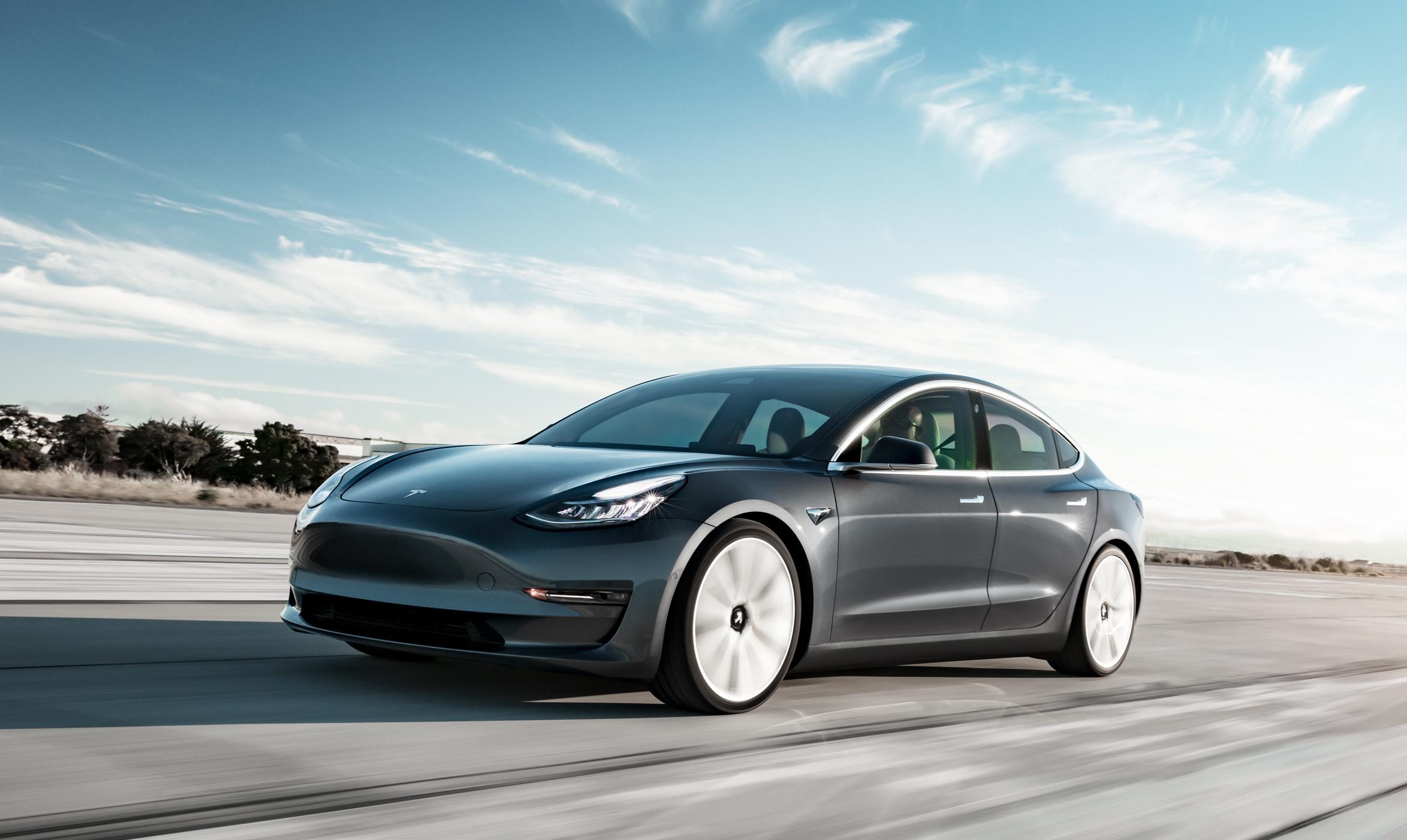 A dark gray Tesla Model 3 Performance, a compact high-performance electric luxury sedan.