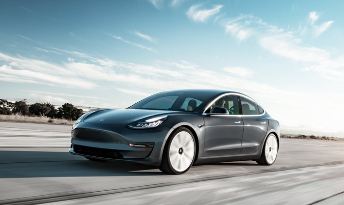A dark gray Tesla Model 3 Performance, a compact high-performance electric luxury sedan.