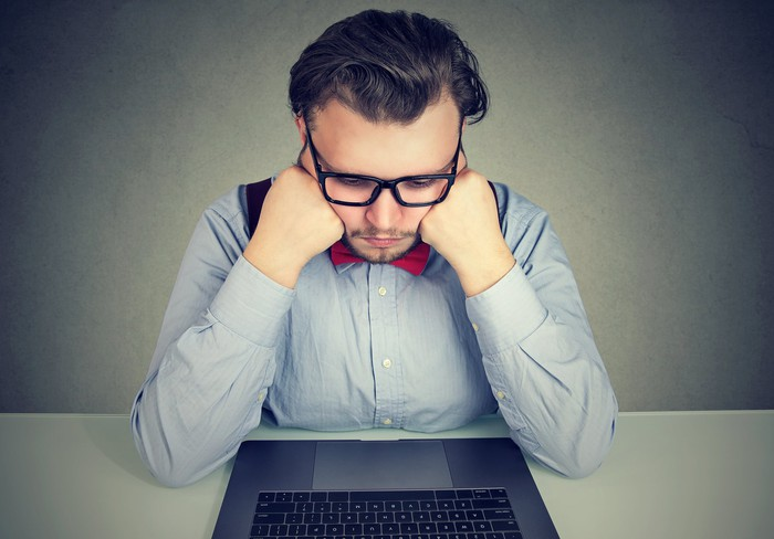 Man looking sad while sitting in front of a laptop.