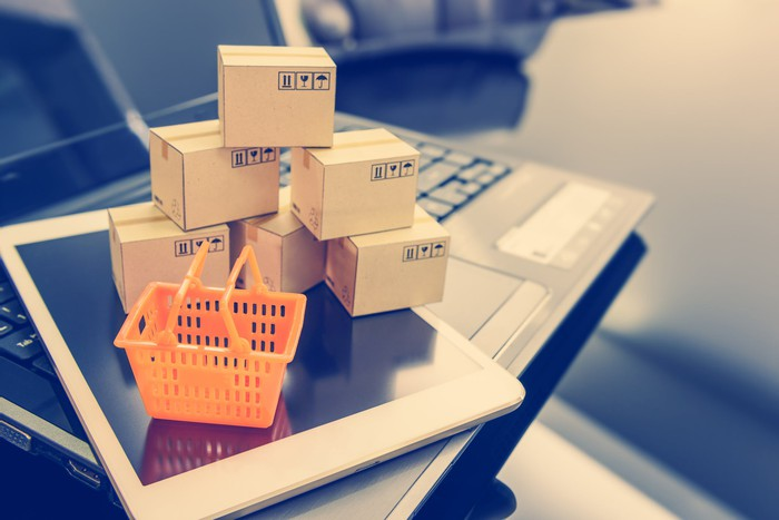 Miniature boxes stacked in a pyramid next to a small orange shopping cart, both of which are lying on a smartphone, which, in turn, is on top of a laptop.