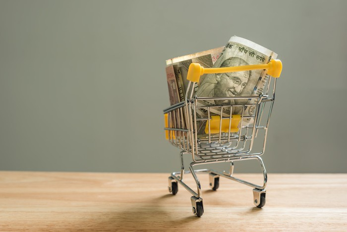 A mini shopping cart filled with rupees.
