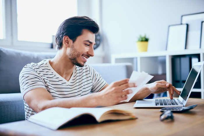 A smiling man holds papers in one hand and types with the other on a laptop.