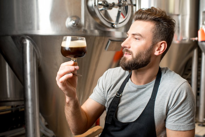 Brewer looking at a snifter of dark beer, with brew tanks in the background
