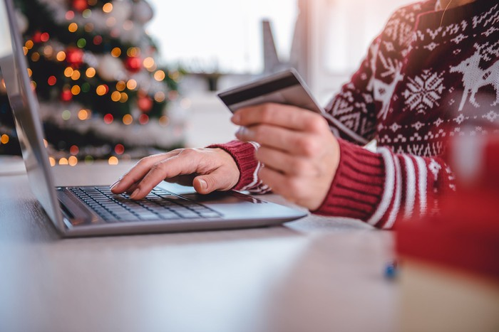 Woman wearing Christmas sweater holding a credit card and typing on a laptop.