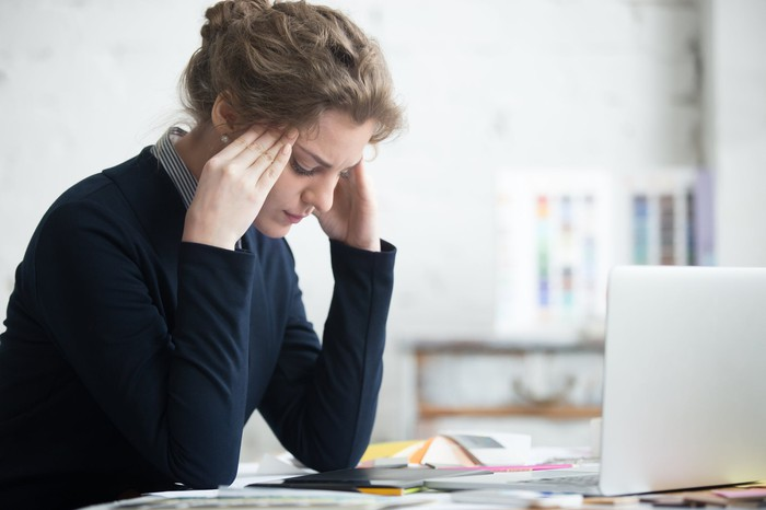 Woman at desk holding her head as if stressed with laptop in front of her