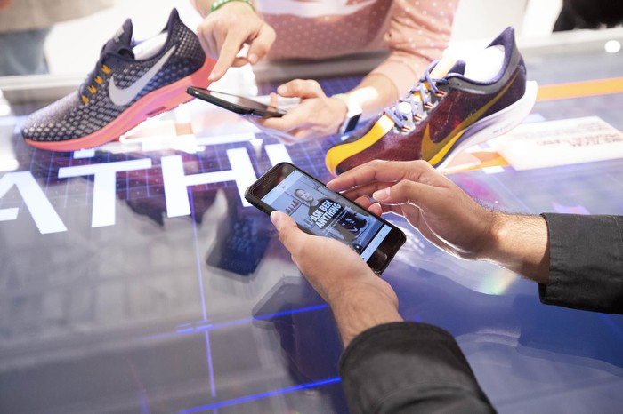 Hands holding a smartphone with the Nike app displayed and two Nike running shoes sitting nearby.
