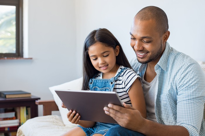 Man holding girl on lap; both are looking at a tablet.