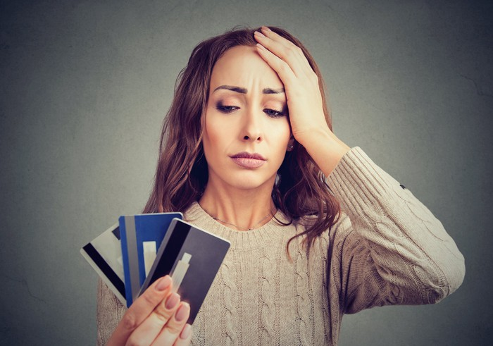 Woman with concerned expression holding her head while holding three credit cards