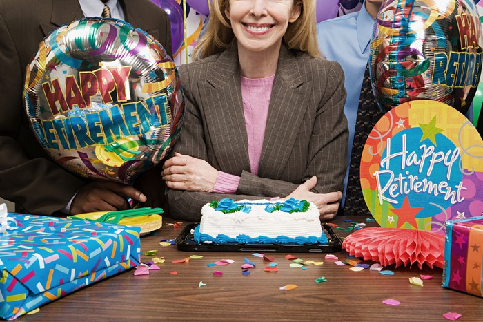 A woman at her retirement party with a cake and balloons