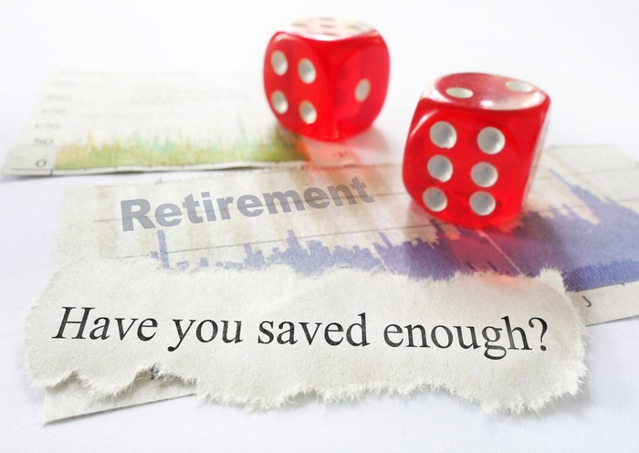 Two red dice on top of a torn piece of paper on which is printed the words Retirement and Have you saved enough?