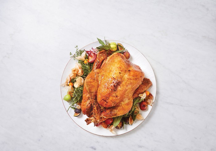 A roasted turkey presented on a serving dish with various herbs and fruits.