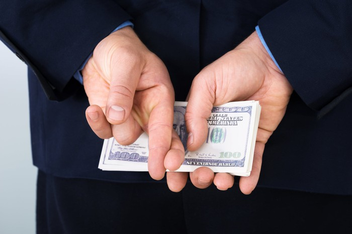 A businessman in a suit holding a stack of hundred dollar bills behind his back while also crossing his fingers.