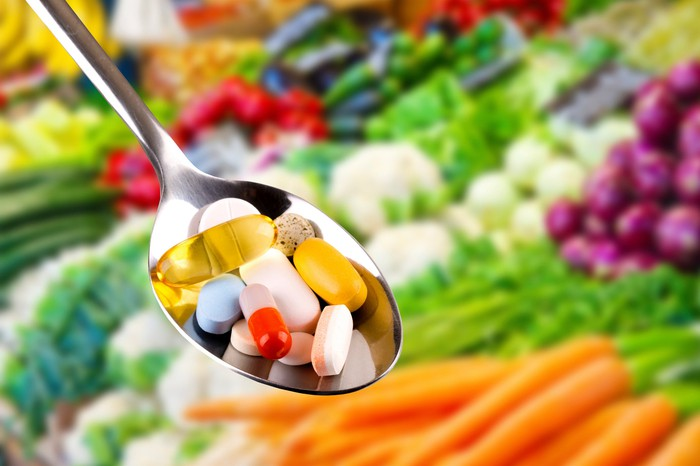 A tablespoon of pills with vegetables in the background.