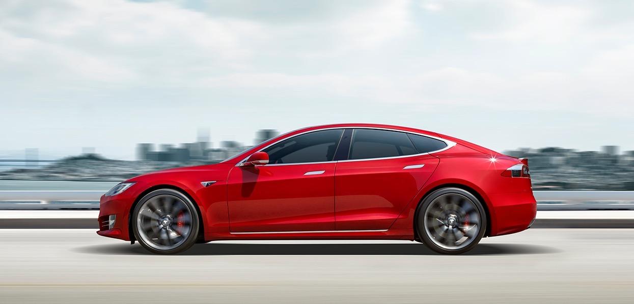A bright red Tesla Model S, a sleek luxury-sports sedan, on a coastal road.