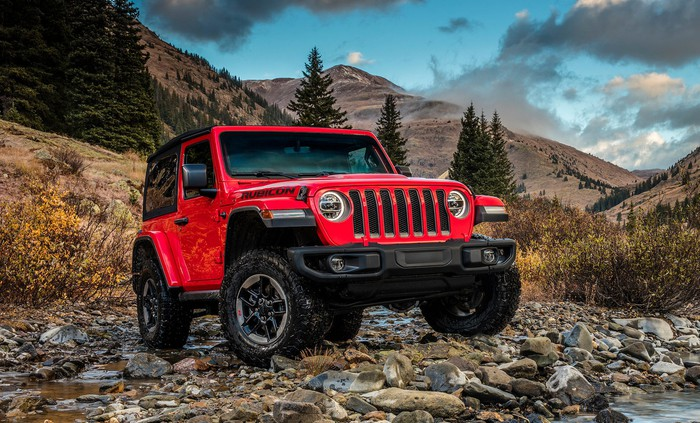 A red 2019 Jeep Wrangler Rubicon, an off-road SUV, on rocky terrain.