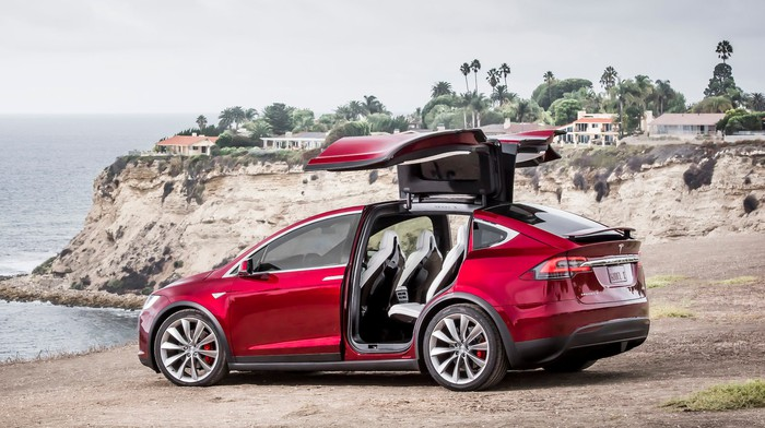 """A red Tesla Model X SUV with its rear """"falcon-wing"""" doors open, parked on a beach."""