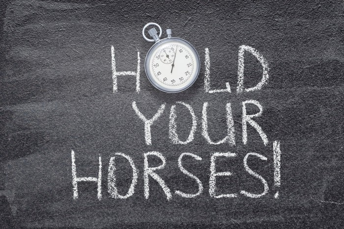 """""""Hold your horses"""" written on chalkboard with a vintage stopwatch used instead of O."""
