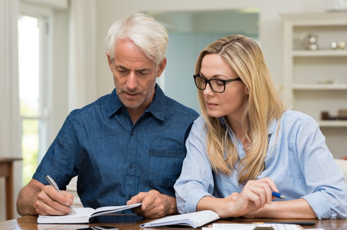 Middle-aged man writing in notebook while woman looks on.