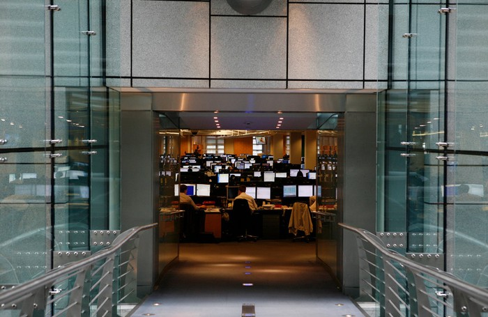 View from a glass hallway of a trading floor with dozens of people and computer monitors.