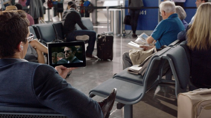 A person sitting in an airport watching a video on a tablet.