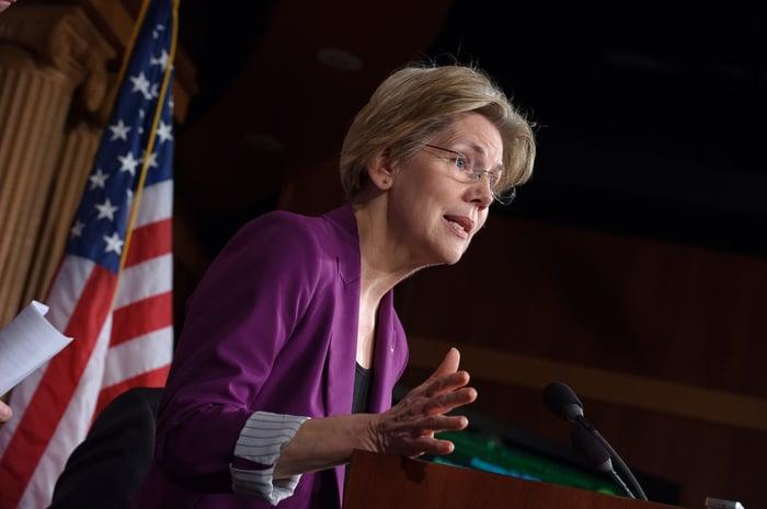 Massachusetts Sen. Elizabeth Warren speaking to reporters from behind a podium.