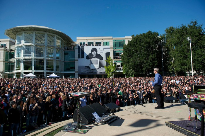 Tim Cook speaks at Apple headquarters with a picture of Jobs in the background.