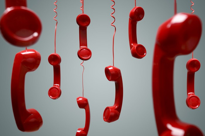 Red phone receivers hanging by their cords.