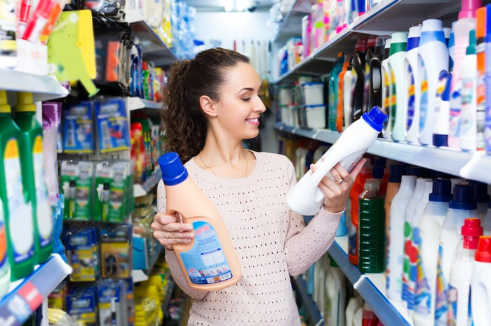 A woman choosing between cleaning supplies.