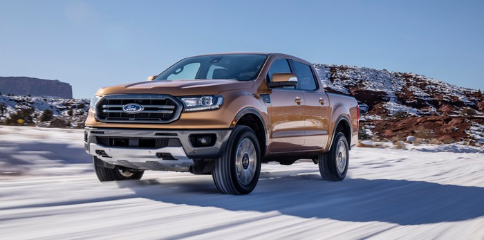An orange 2019 Ford Ranger, a midsize pickup truck, on a snowy road.