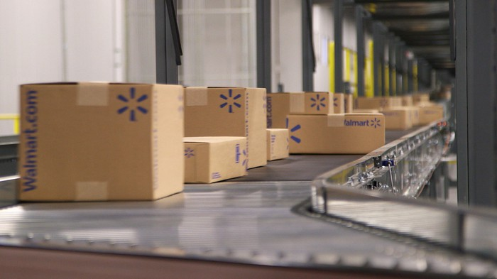 Several boxes with the Walmart.com logo move down the line in a Walmart shipping facility.