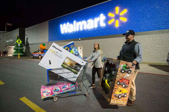 A man and a woman push a cart full of items in a parking lot outside of a Walmart store with the Walmart logo displayed on the side of the store in the background.