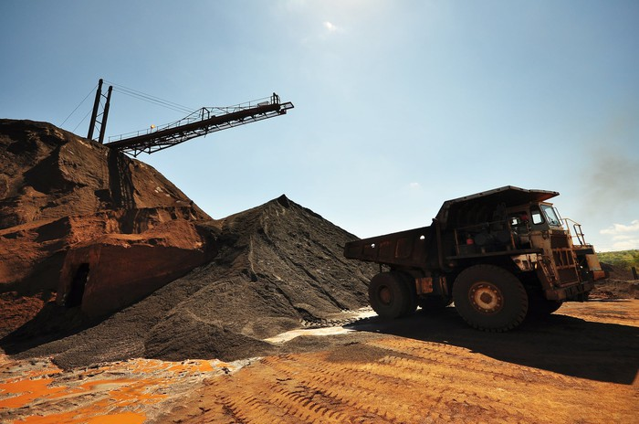 A dump truck and a crane near a heap of ore at a mine.