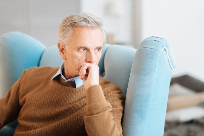 Older man deep in thought sitting in light-blue chair.