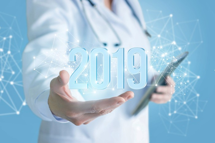 Physician with stethoscope around neck holding tablet in one hand and extending other hand with an image of 2019 appearing above the hand and connected points of light in the foreground