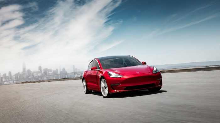 A red Tesla Model 3 with a city skyline in the background