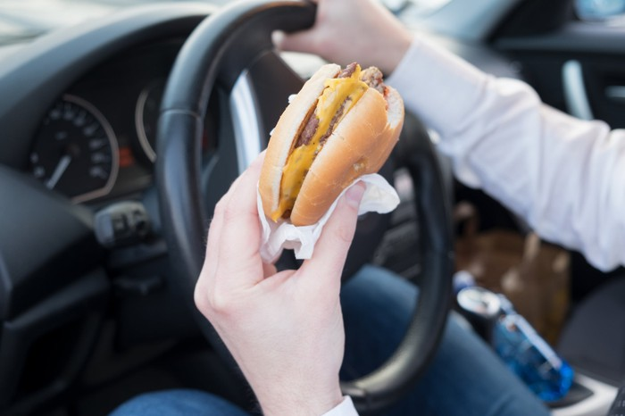 In a car's interior, the driver's hand holds a burger while the other grips the steering wheel.