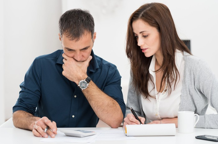 Man and woman at table; man has calculator in front of him while woman takes notes.