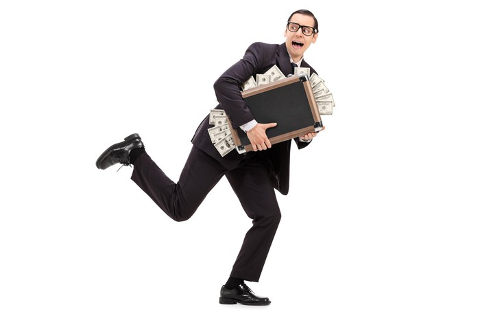 Frightened person running with a briefcase bursting with cash.