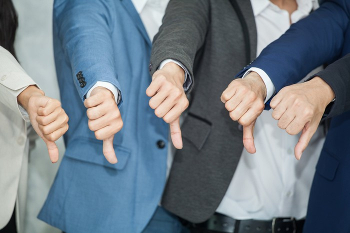 Five men wearing suits with their arms extended out, giving a thumbs-down