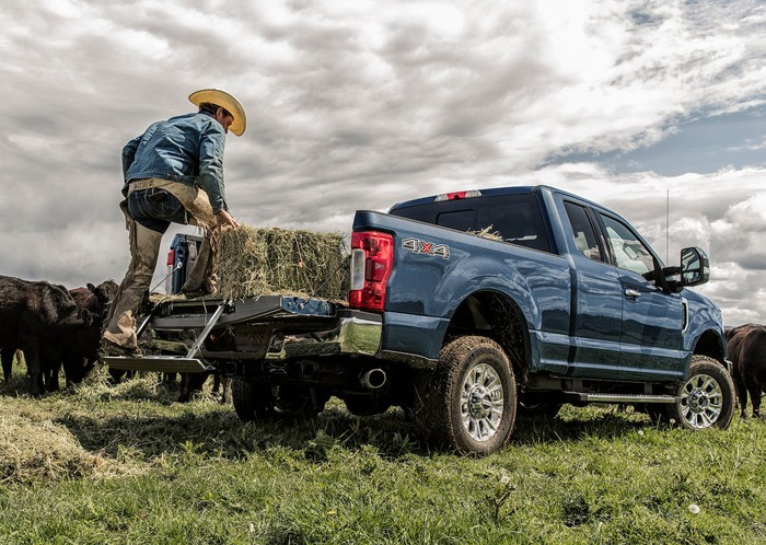 A rancher is shown unloading a hay bale from a blue 2019 Ford F-350 XLT, a heavy-duty full-size pickup. Cattle are visible in the background.