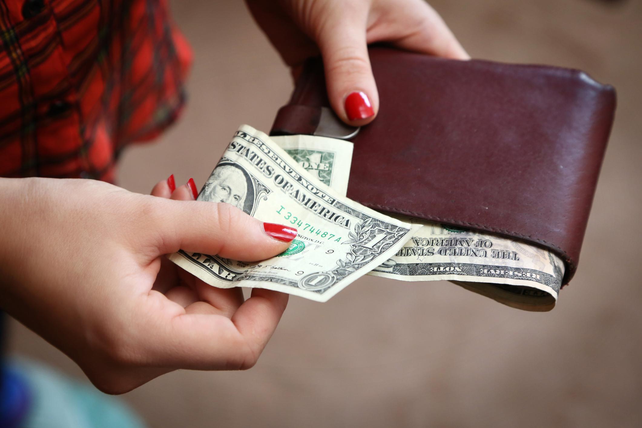 Woman taking one-dollar bill from wallet