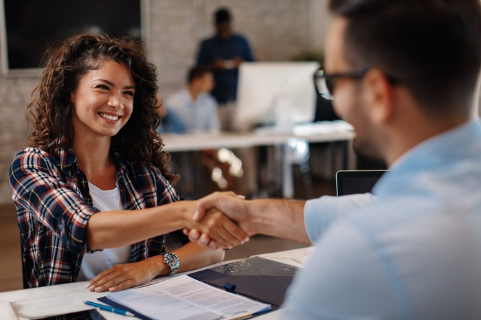 Smiling woman shaking hands with man across the table.