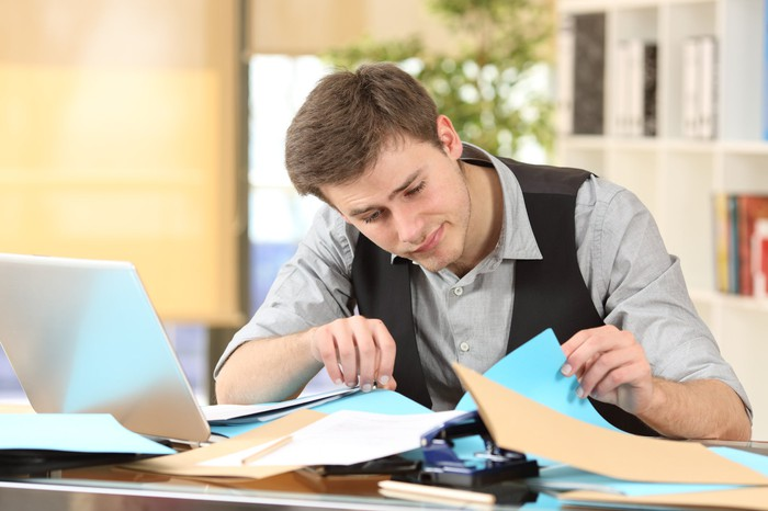 Man searching for something underneath folders on a messy desk.