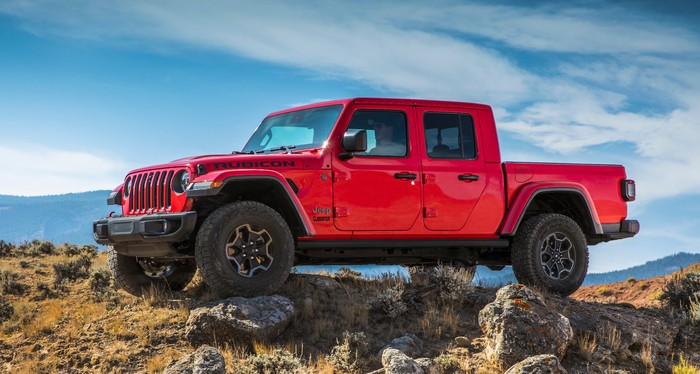A red Jeep Gladiator, a pickup truck based on the Jeep Wrangler Unlimited off-road SUV.