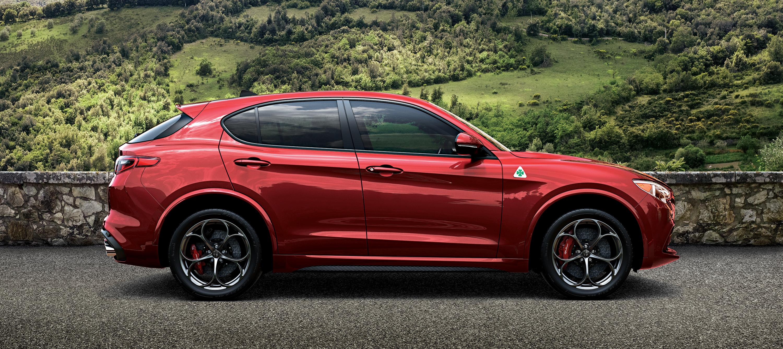A red Alfa Romeo Stelvio, a high-performance 5-passenger luxury-sports crossover SUV.